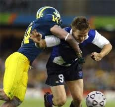 Football player tackles soccer player